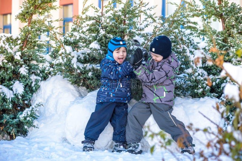 Deux garçons de petit enfant dans des vêtements colorés jouant dehors pendant les chutes de neige Loisirs actifs avec des enfants photographie stock