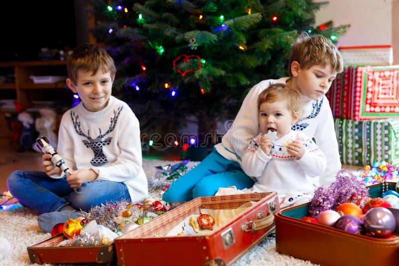 Deux garçons de petit enfant et bébé adorable décorant l'arbre de Noël avec de vieux jouets et boules de vintage famille photo stock