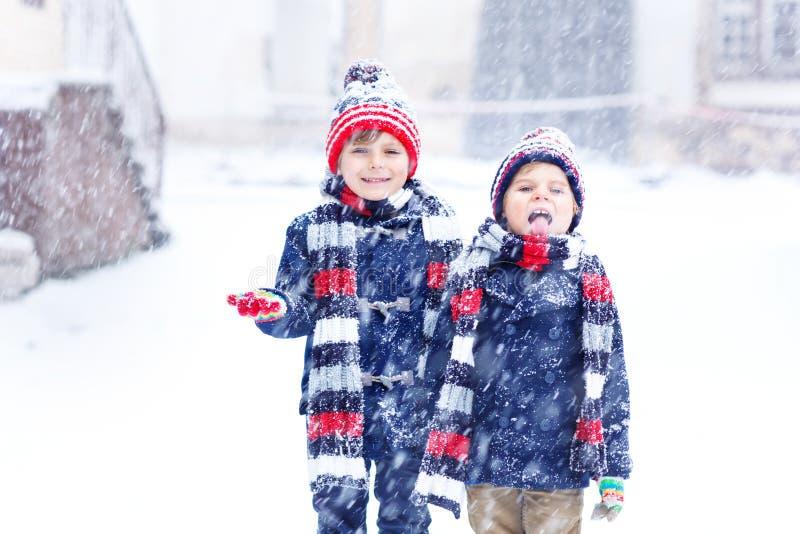 Deux garçons de petit enfant de mode colorée vêtx jouer dehors pendant les chutes de neige fortes Loisirs actifs avec des enfants photos stock