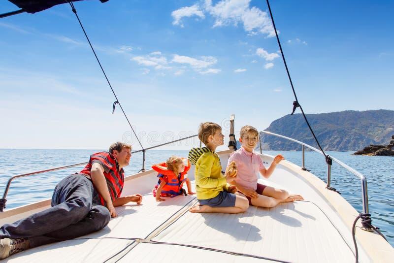 Deux garçons de petit enfant, père et fille d'enfant en bas âge appréciant le voyage de bateau à voile Vacances de famille sur l' photos stock