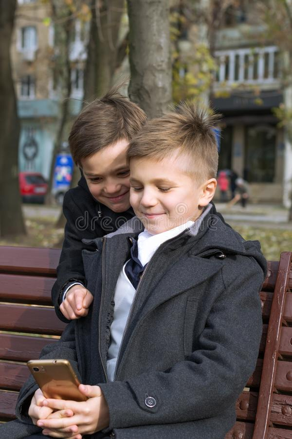 Deux garçons en tenue d'affaires sur un banc dans le parc par jour d'automne Les enfants regardent quelque chose d'intéressant su photographie stock