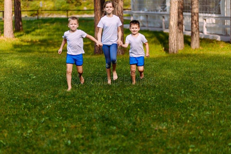 Deux garçons et une fille de dix ans courant sur l'herbe verte Enfants de sourire heureux en été images libres de droits