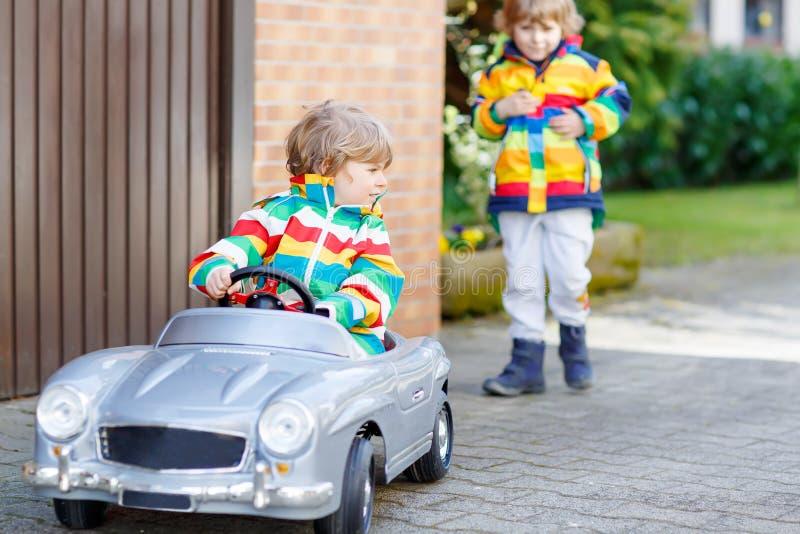 Deux garçons heureux d'enfant de mêmes parents jouant avec la grande vieille voiture de jouet photos libres de droits