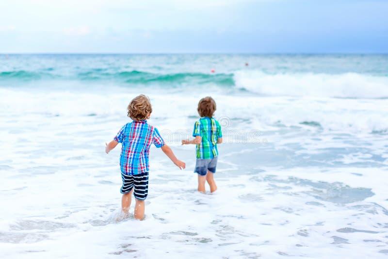 Deux garçons heureux de petits enfants courant sur la plage de l'océan Enfants, enfant de mêmes parents drôle et meilleurs amis m photographie stock libre de droits