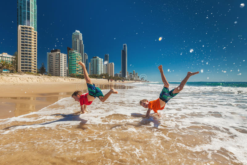 Deux garçons heureux faisant la main se tient sur la plage de la Gold Coast, Australie photo stock