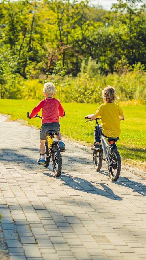 Deux garçons heureux faisant un cycle dans le FORMAT VERTICAL de parc pour l'histoire d'Instagram ou la taille mobile d'histoires image stock