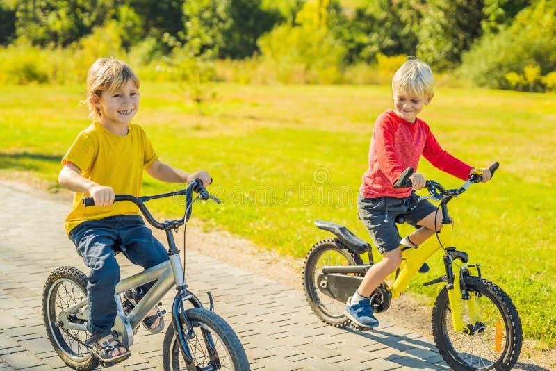 Deux garçons heureux faisant un cycle en parc photos stock