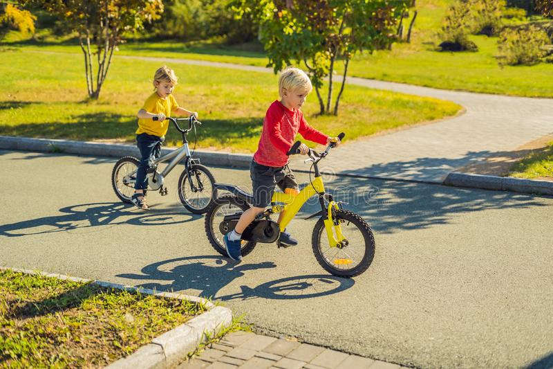 Deux garçons heureux faisant un cycle en parc photo libre de droits