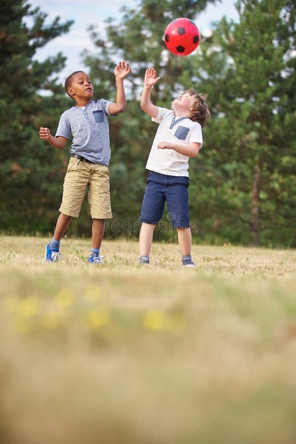 Deux garçons jetant la boule dans le ciel image stock