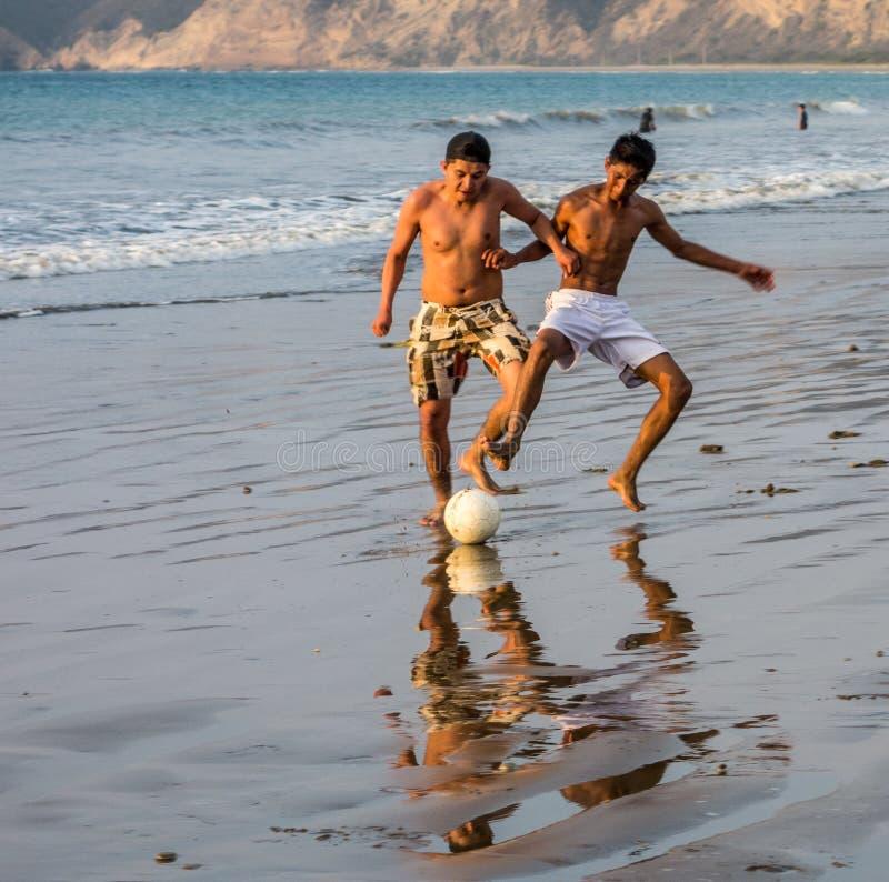 Deux garçons jouent au football sur une plage dans les salines, Equateur image libre de droits