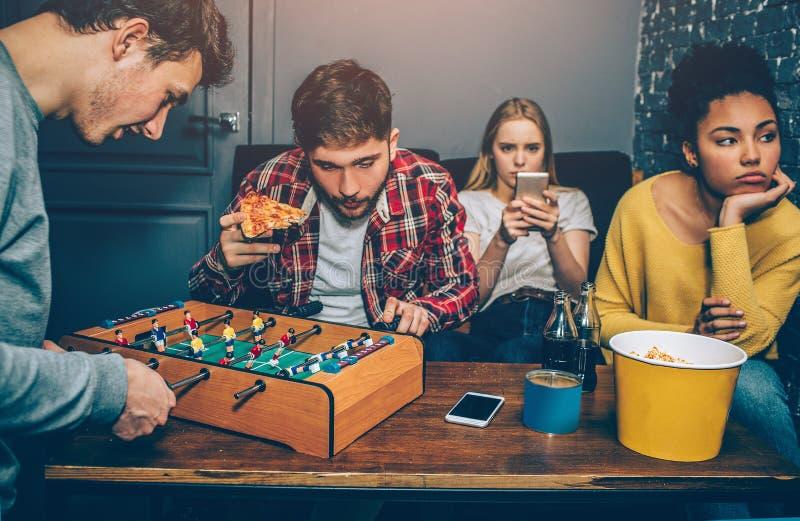 Deux garçons jouent la partie de football de conseil Ils sont très concentrés là-dessus tandis que les filles observent dans le t image stock