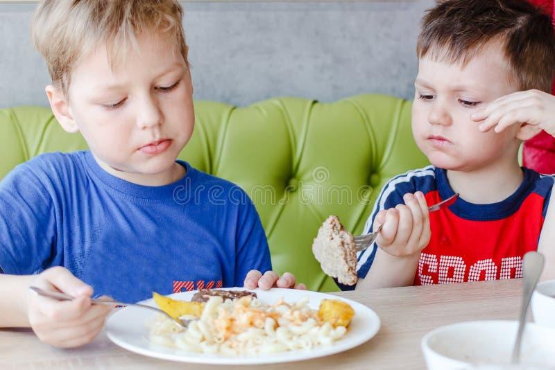 Deux garçons mangeant des pâtes avec une côtelette photos libres de droits