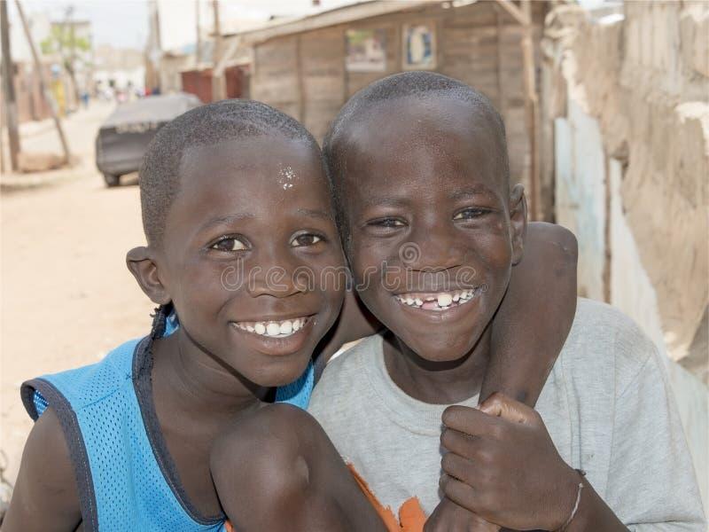 Deux garçons non identifiés se tenant dans la rue, secteur populaire des rails de Guinaw photographie stock libre de droits