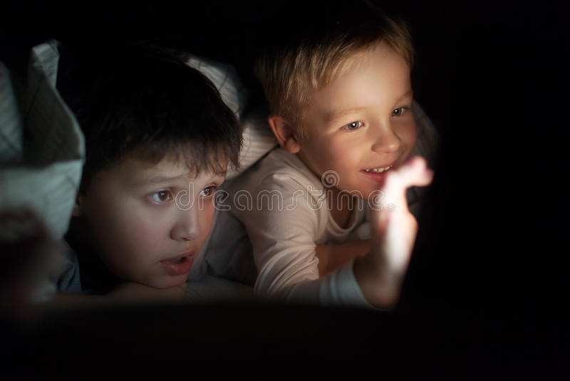 Deux garçons observant le film ou la bande dessinée sur la protection la nuit photographie stock
