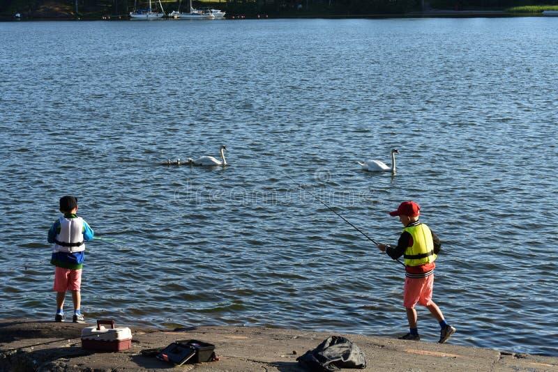 Deux garçons pêchant du lac photo stock