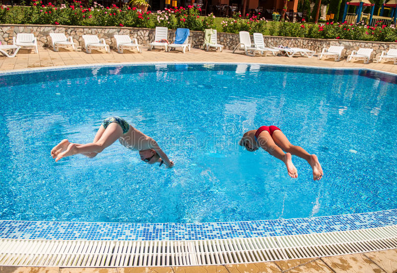 Deux garçons plongeant dans une piscine photo stock
