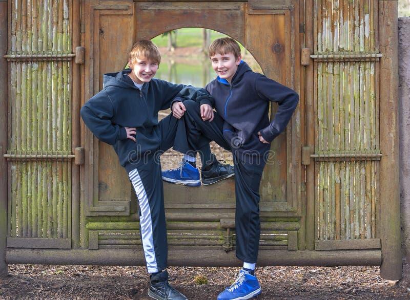 Deux garçons posant dans un cadre en bambou en parc public image libre de droits