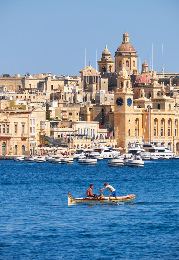 Deux garçons ramant dans le bateau sur l'eau du port grand avec t images stock