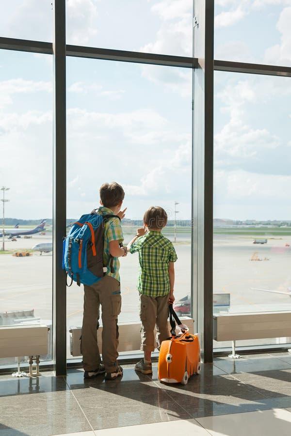 Deux garçons regardent le champ de vol dans le terminal d'aéroport photographie stock libre de droits