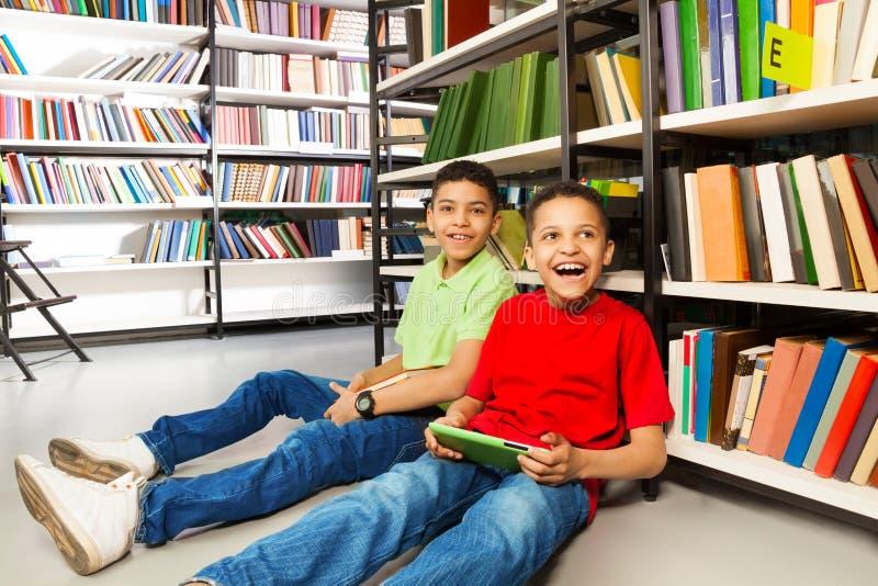 Deux garçons riants s'asseyant sur le plancher dans la bibliothèque photographie stock