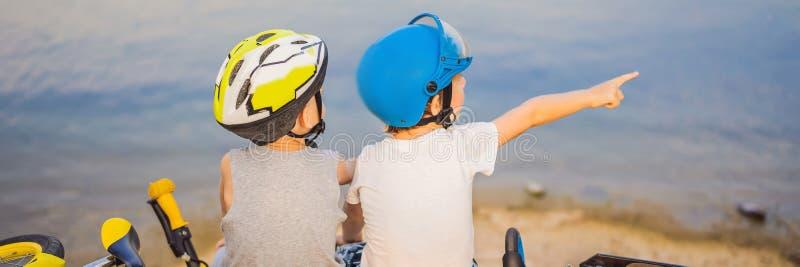 Deux garçons s'asseyent sur le rivage du lac après la monte d'une BANNIÈRE de vélo et de scooter, LONG FORMAT image libre de droits