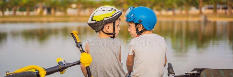 Deux garçons s'asseyent sur le rivage du lac après la monte d'une BANNIÈRE de vélo et de scooter, LONG FORMAT photographie stock libre de droits
