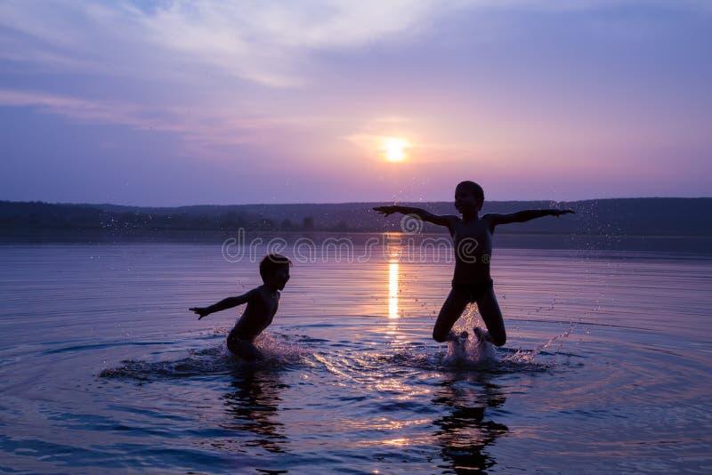 Deux garçons sautant dans l'eau sur le coucher du soleil image libre de droits