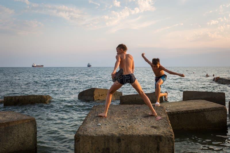 Deux garçons sautant sur des blocs de béton sur le bord de la mer photo stock