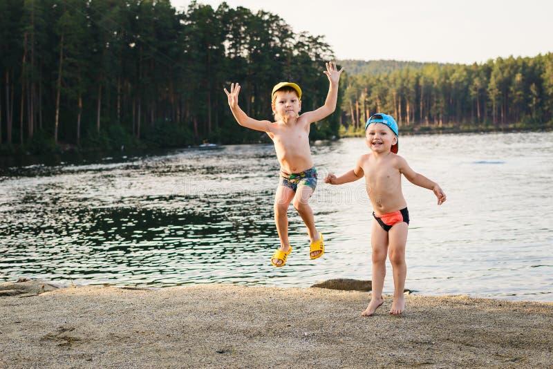 Deux garçons sautant sur le lac image libre de droits