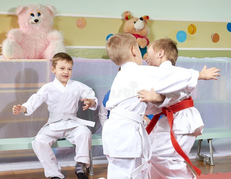 Deux garçons sont boxe d'entraînement qualifiée de judo avant d'autres athlètes images libres de droits
