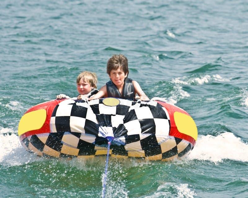 Deux garçons sur le tube derrière le bateau image stock