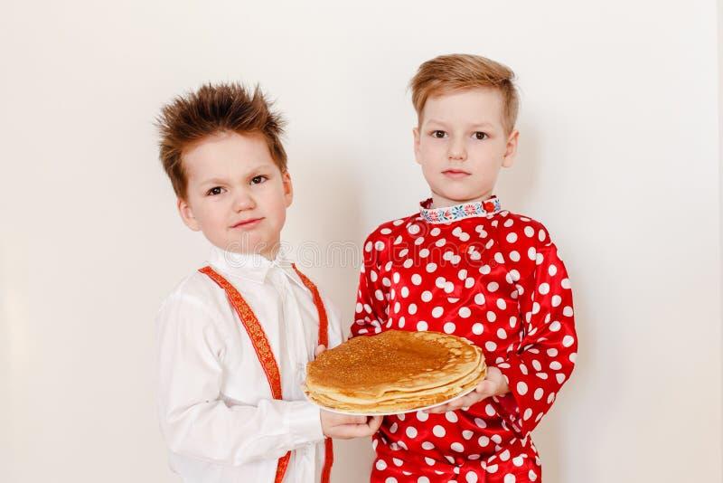 Deux garçons tenant un plat des crêpes images stock