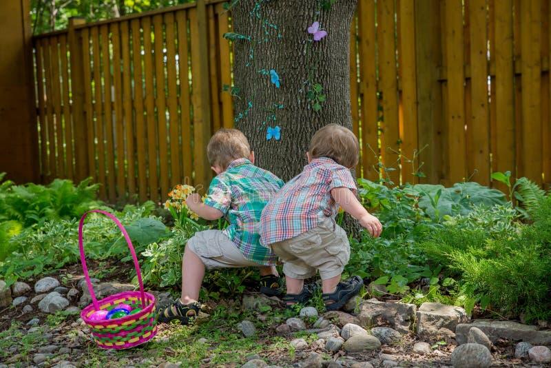 Deux garçons trouvent des oeufs de pâques images stock