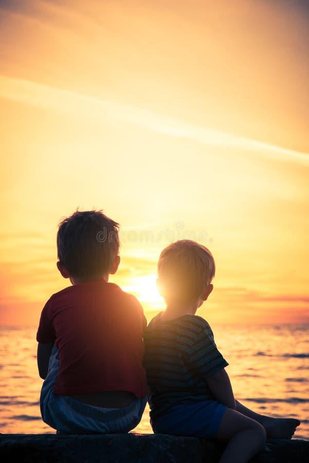 Deux gar?ons s'asseyant sur la roche ? la plage au coucher du soleil images libres de droits
