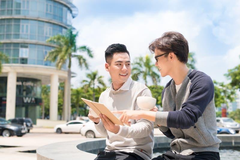 Deux gens d'affaires asiatiques gais discutant avec des documents photo libre de droits
