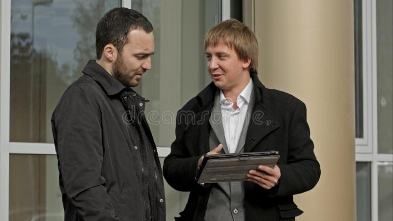 Deux gens d'affaires extérieurs avec le comprimé image stock