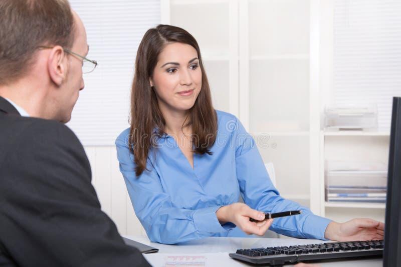 Deux gens d'affaires parlant ensemble au bureau - conseiller et custo image stock
