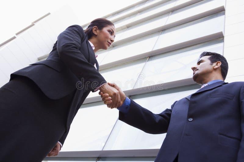 Deux gens d'affaires se serrant la main en dehors de bureau photos libres de droits