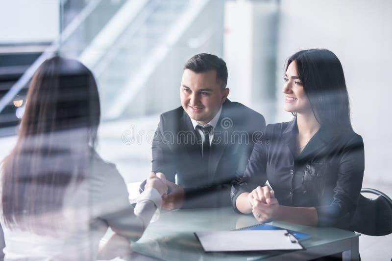 Deux gens d'affaires se serrant la main sur une affaire avec le foyer à un jeune couple posé à un bureau avec l'homme souriant et photos libres de droits