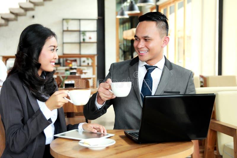 Deux gens d'affaires semblent heureux tout en ayant une pause-café image stock