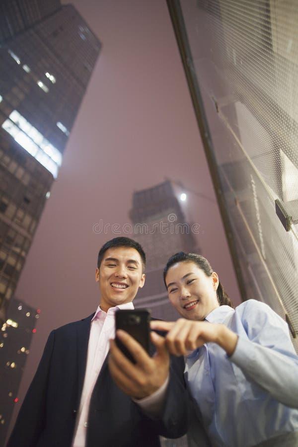 Deux gens d'affaires souriant et regardant le téléphone, dirigeant, dehors la nuit, la vue d'angle faible photographie stock libre de droits