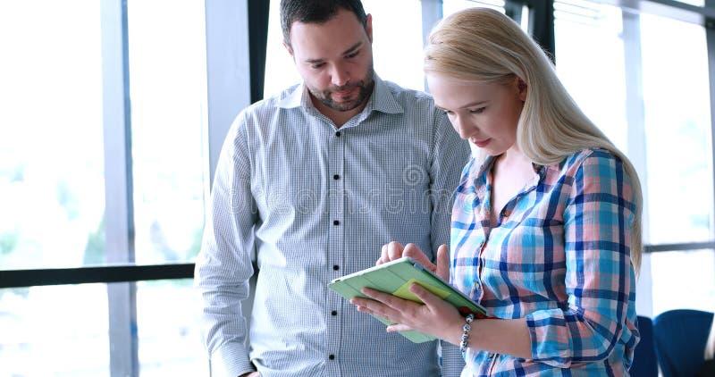 Deux gens d'affaires travaillant avec la Tablette dans le bureau de démarrage photographie stock libre de droits