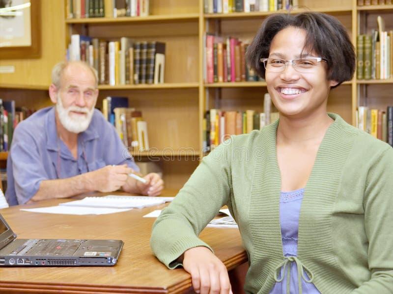 Deux gens de sourire, vieil homme européen et fille africaine, dans librar photographie stock
