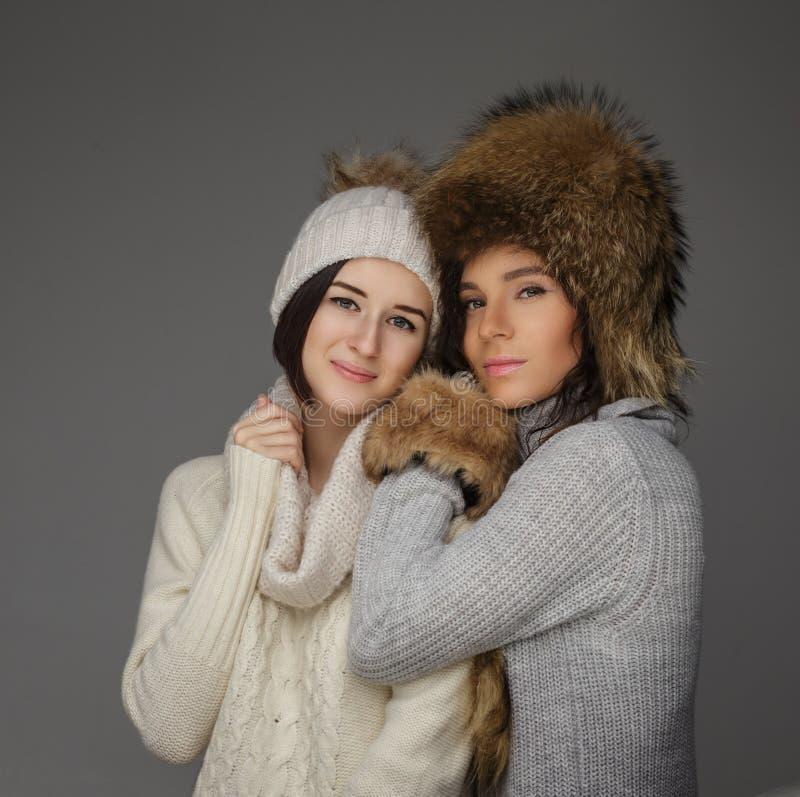 Deux gentilles filles dans les vêtements d'hiver et des chapeaux de fourrure chauds photo libre de droits