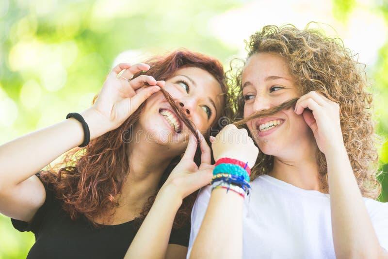 Deux girs faisant la moustache avec leurs cheveux photos stock