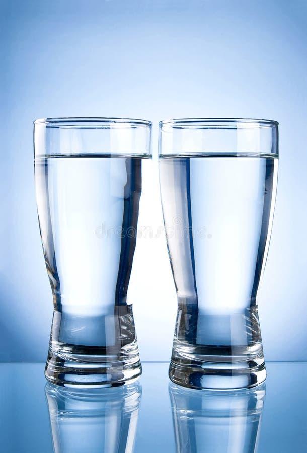 Deux glaces de l'eau sur un bleu photographie stock