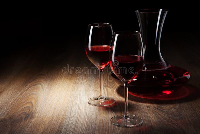 Deux glaces et décanteurs de vin sur une table en bois images stock