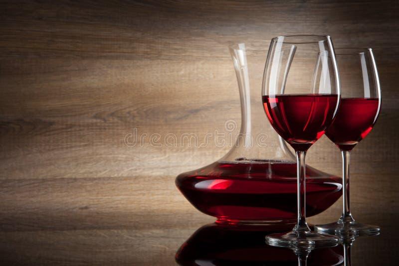 Deux glaces et décanteurs de vin sur une table en bois photos stock