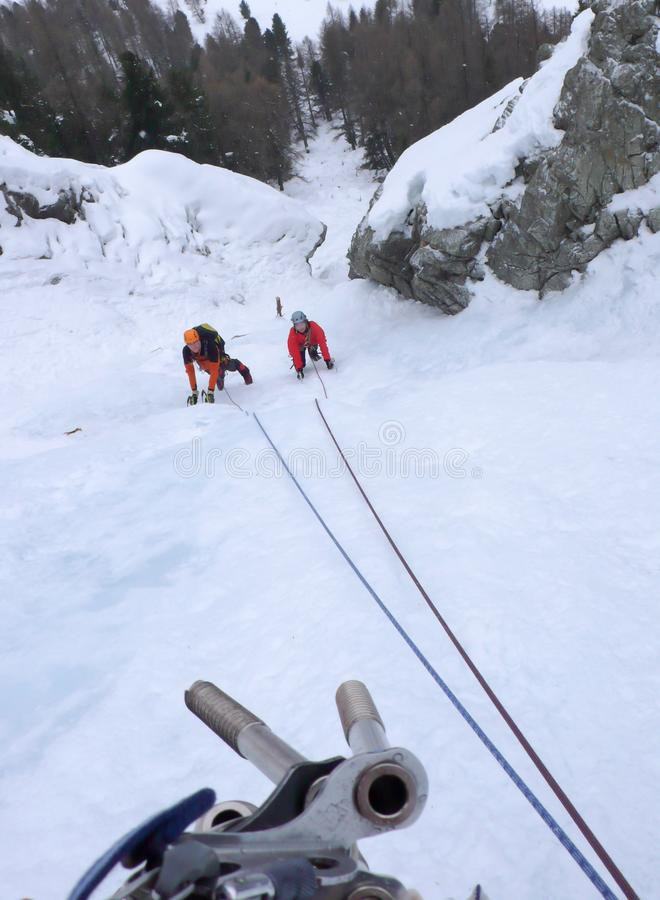 Deux glaciéristes sur un icefall raide en hiver dans les Alpes de la Suisse photographie stock