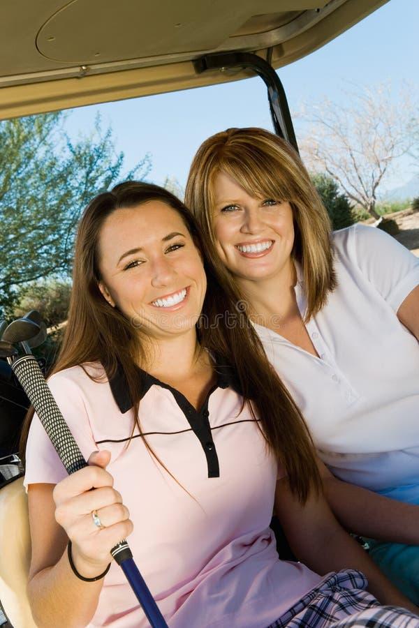 Deux golfeurs de femmes s'asseyant dans le chariot de golf images stock